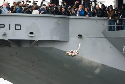 In New York City, on Dec. 7, 2016, two survivors, Aaron Chabin, 93, and Clark Simmons, 95, toss a wreath into the Hudson River while engulfed by members of the media from the USS Intrepid, an aircraft carrier turned museum.