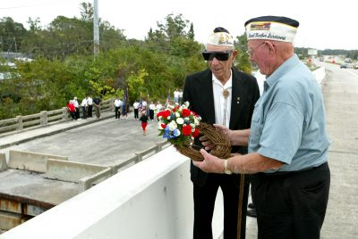 From Pearl Harbor Day, 2004, survivors Michael J. Tiberio and Ed Warren prepare to toss a wreath of remembrance into the Little Manatee River in Ruskin. The events were organized by the Ruskin VFW Post Ladies Auxiliary. By 2006, only one survivor remained for the ceremony.